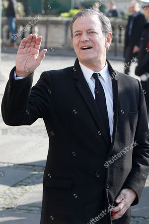 French actor Francis Huster waves as he arrives to attend the funeral of French director Alain Resnais in the Saint Vincent de Paul church in Paris, . The French director died at age 91 on march 1, 2014, in Paris