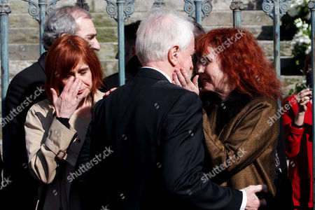 French actress and Alain Resnais' wife, Sabine Azema, right, hugs actor Andre Dussolier, at the end of the funeral service for Alain Resnais in the Saint Vincent de Paul church in Paris, . The French director died at age 91 on March 1, 2014, in Paris