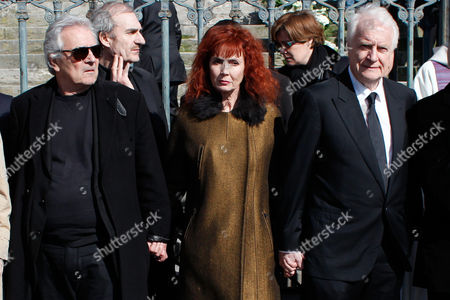 French actress and Alain Resnais' wife, Sabine Azema, center, actors Andre Dussolier, right, and Pierre Arditi, pay respect at the end of the funeral service for Resnais in the Saint Vincent de Paul church in Paris, . The French director died at age 91 on March 1, 2014, in Paris