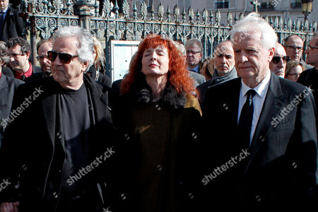 French actress and Alain Resnais' wife, Sabine Azema, center, actors Andre Dussolier, right, and Pierre Arditi, pay respect at the end of the funeral service for Alain Resnais in the Saint Vincent de Paul church in Paris, . The French director died at age 91 on March 1, 2014, in Paris