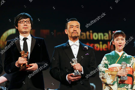From left, director Diao Yinan with the Golden Bear for Best Film, actor Fan Liao with the Silver Bear for best actor, both for the film Black Coal, Thin Ice, and actress Haru Kuroki with the Silver Bear for Best Actress for the movie The Little House, acknowledge applause after the presentation during the award ceremony at the International Film Festival Berlinale in Berlin