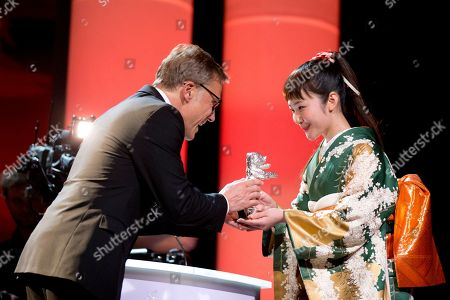 Actress Haru Kuroki, right, is awarded the Silver Bear Best Actress award for the movie The Little House, by jury member Christoph Waltz, during the award ceremony at the International Film Festival Berlinale in Berlin