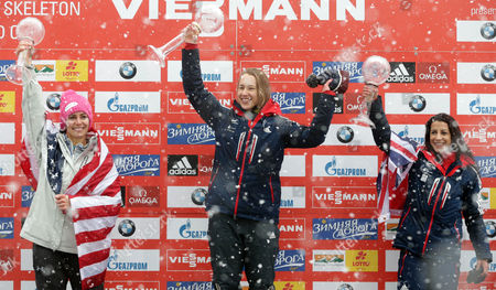 Overall world cup winner Elizabeth Yarnold of Britain, center, celebrates with the trophy besides overall second placed Noelle Pikus-Pace of the United States, left, and third placed Shelley Rudman of Britain during the overall world cup ceremony at the women's Skeleton World Cup in Koenigssee, southern Germany, on