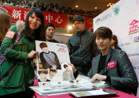 Kim Woo Bin South Korean actor and model Kim Woo Bin poses for a photo while giving a fan a poster with his autograph during a meeting in Hong Kong