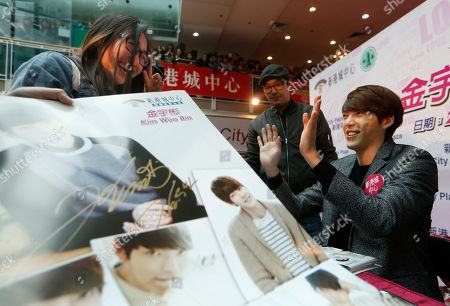 Kim Woo Bin South Korean actor and model Kim Woo Bin, right, waves to his fan as he gives his autograph during a meeting in Hong Kong