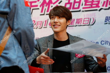 Kim Woo Bin South Korean actor and model Kim Woo Bin gives his poster with his autograph to a fan during a meeting in Hong Kong