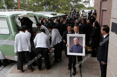 "A relative, holding a portrait of Hong Kong movie producer Run Run Shaw, attends the funeral at Cape Collinson Crematorium in Hong Kong, . Shaw built a Hong Kong movie and TV empire that nurtured rising talents like actor Chow Yun-fat and director John Woo, inspired Hollywood filmmakers such as Quentin Tarantino and produced the 1982 sci-fi classic ""Blade Runner."" Pioneering Hong Kong movie producer Shaw died on Tuesday at the age of 107"