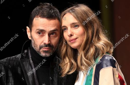 Italian designer Fabio Novembre is flanked by his wife Candela during the Roberto Cavalli men's Fall-Winter 2014 collection, part of the Milan Fashion Week, unveiled in Milan, Italy, Tuesday, Jan.14, 2014