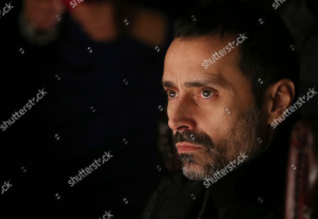 Italian designer Fabio Novembre watches during Roberto Cavalli men's Fall-Winter 2014 collection, part of the Milan Fashion Week, unveiled in Milan, Italy, Tuesday, Jan.14, 2014