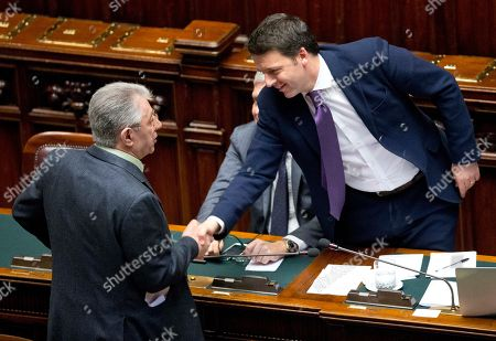 Italian premier Matteo Renzi, right, shakes hands with Northern League party lawmaker Umberto Bossi prior to a confidence vote in the Chamber of Deputies, in Rome, . The Senate voted 169-139 to confirm Renzi's broad coalition, which ranges from his center-left Democrats to center-right forces formerly loyal to ex-premier Silvio Berlusconi. Renzi needed at least 155 votes to clinch the victory, one of two mandatory confidence votes. The second vote, in the Chamber of Deputies, is expected later Tuesday. Renzi's coalition has a comfortable majority in the lower chamber