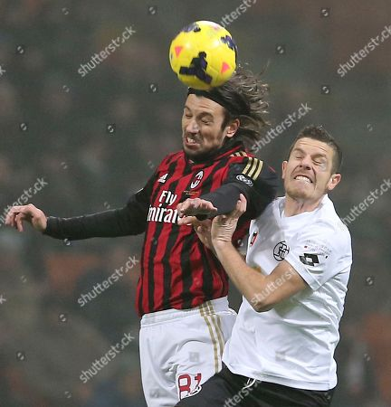 AC Milan defender Cristian Zaccardo, left, jumps for the ball with Spezia forward Andrea Catellani during the Italian Cup soccer match between AC Milan and Spezia at the San Siro stadium in Milan, Italy