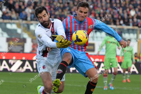 Catania forward Gonzalo Bergessio, right, of Argentina, challenges for the ball with Bologna goalkeeper Gianluca Curci during the Serie A soccer match between Catania and Bologna at the Angelo Massimino stadium in Catania, Italy