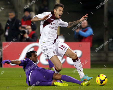 Fiorentina's Juan Cuadrado, of Colombia, left, fights for the ball with Livorno's Leandro Greco during a Serie A soccer match at the Artemio Franchi stadium in Florence, Italy