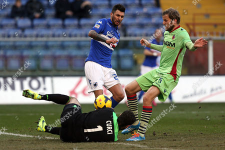 Stock Picture of Bologna goalkeeper Gianluca Curci,bottom, saves on Sampdoria midfielder Roberto Soriano, first from left, during a Serie A soccer match between Sampdoria and Bologna, in Genoa, Italy
