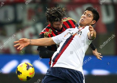 AC Milan defender Cristian Zaccardo, left, challenges for the ball with Bologna forward Jonatan Cristaldo, of Argentina, during the Serie A soccer match between AC Milan and Bologna at the San Siro stadium in Milan, Italy