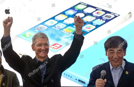 Stock Image of Tim Cook, Xi Guohua Apple's CEO Tim Cook, left, gestures as China Mobile Chairman Xi Guohua smiles during a promotional event that marks the opening day of sales of China Mobile's 4G iPhone 5s and iPhone 5c in Beijing, China. Soaring sales of iPhones in China, Russia, India and Brazil during the April-June 2014 period helped Apple overcome softening demand for the device in the U.S. and Europe, where consumers seem to be more interested in waiting for the autumn release of a new iPhone that's expected to feature a larger screen