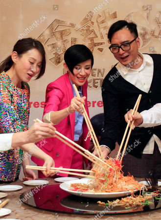 "Sandra Ng, Ivana Wong, Matt Chow Hong Kong actresses Ivana Wong, left, Sandra Ng, center, and Hong Kong director Matt Chow toss and mix ""yee sang,"" or raw fish salad, after a press conference to promote their new film ""Golden Chicken SSS"" in Petaling Jaya, near Kuala Lumpur, Malaysia"