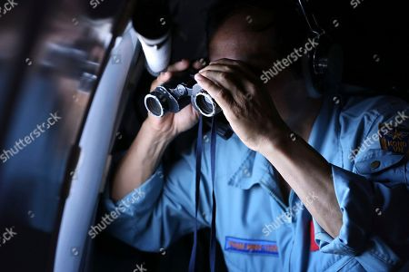 Vietnamese Air Force Col. Pham Minh Tuan uses binoculars on board a flying aircraft during a mission to search for the missing Malaysia Airlines flight MH370 in the Gulf of Thailand, . With no distress call, no sign of wreckage and very few answers, the disappearance of the Malaysia Airlines plane is turning into one of the biggest aviation mysteries since Amelia Earhart vanished over the Pacific Ocean in 1937