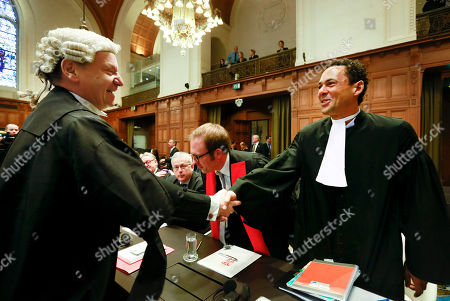Counsel Philippe Sands of Croatia, left, shakes hands with Wayne Jordash of the Serbia delegation, right, prior to the start of public hearings at the International Court of Justice (ICJ) in The Hague, Netherlands, . Croatia is accusing Serbia of genocide during fighting in the early 1990's as the former Yugoslavia shattered in spasms of ethnic violence, in a case at the United Nations' highest court that highlights lingering animosity in the region. Croatia is asking the ICJ to declare that Serbia breached the 1948 Genocide Convention when forces from the former Federal Republic of Yugoslavia attempted to drive Croats out of large swaths of the country after Zagreb declared independence in 1991