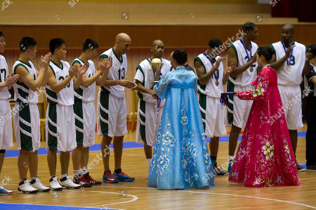 """Doug Christie, Andre """"Silk"""" Poole, Guy Dupree, Charles D. Smith, Cliff Robinson U.S. basketball player Doug Christie is handed a trophy as North Korean players applaud at the end of an exhibition basketball game at an indoor stadium in Pyongyang, North Korea on . The U.S. players, from left to right, are Christie, Andre """"Silk"""" Poole, Guy Dupree, Charles D. Smith, and Cliff Robinson"""