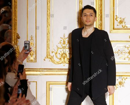 Jordan-born fashion designer Rad Hourani reacts after the presentation of his Spring-Summer 2014 Haute Couture fashion collection presented in Paris, Wednesday, Jan.22, 2014