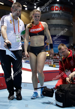 Germany's Silke Spiegelburg is led of the venue after falling during an attempt in the women's pole vault at the Athletics Indoor World Championships in Sopot, Poland