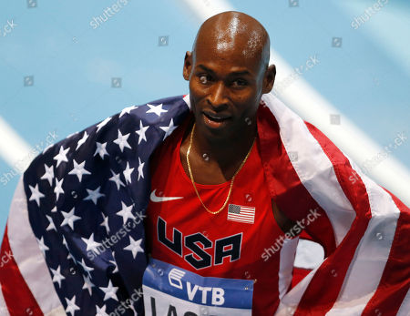 United States' Bernard Lagat carries the US flag after finishing second in the 3000 m finalduring the Athletics World Indoor Championships in Sopot, Poland