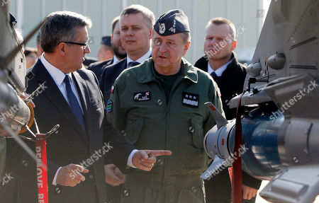 Bronislaw Komorowski, Lech Majewski Poland's President Bronislaw Komorowski, left, and the commander of Poland's Air Force, Gen. Lech Majewski, right, talk during a visit to Lask airbase, central Poland,. President Komorowski says he would like more U.S. troops in the country to guarantee its security within NATO, which Poland joined 15 years ago this week. Komorowski marked the anniversary with a visit to the air base in Lask, in central Poland, where a Polish F16 fighter force is based, along with 10 U.S. airmen who support rotating visits of American pilots and aircraft. On a request that Warsaw made after Russian troops took control of Ukraine's Crimea, some 300 U.S. airmen and a dozen F16 fighters are expected in Poland this week. They will take part in joint exercises