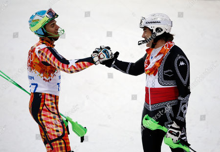 Mexico's Hubertus von Hohenlohe, right, and East Timor's Yohan Goncalves Goutt shake hands after von Hohenlohe crashed during first run of the men's slalom at the Sochi 2014 Winter Olympics, in Krasnaya Polyana, Russia