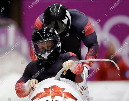 The team from Canada CAN-1, piloted by Lyndon Rush and brakeman Lascelles Brown, start their first run during the men's two-man bobsled competition at the 2014 Winter Olympics, in Krasnaya Polyana, Russia