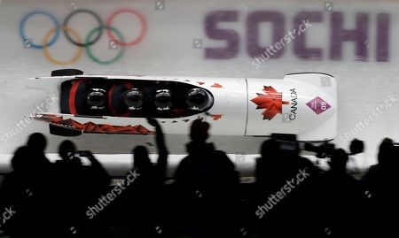 Stock Photo of The team from Canada CAN-2, with Lyndon Rush, Lascelles Brown, David Bissett and Neville Wright, take a curve during the men's four-man bobsled competition at the 2014 Winter Olympics, in Krasnaya Polyana, Russia