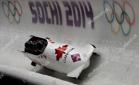 Stock Image of The team from Canada CAN-2, with Lyndon Rush, Lascelles Brown, David Bissett and Neville Wright, take a curve on their second run during the men's four-man bobsled competition at the 2014 Winter Olympics, in Krasnaya Polyana, Russia