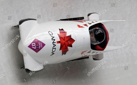 The team from Canada CAN-1, piloted by Lyndon Rush and brakeman Lascelles Brown, take a curve during the men's two-man bobsled competition at the 2014 Winter Olympics, in Krasnaya Polyana, Russia
