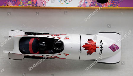 The team from Canada CAN-1, piloted by Lyndon Rush and brakeman Lascelles Brown, take a turn during the men's two-man bobsled competition at the 2014 Winter Olympics, in Krasnaya Polyana, Russia