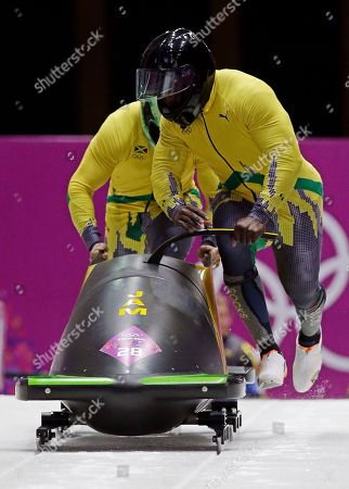 The team from Jamaica JAM-1, piloted by Winston Watts and brakeman Marvin Dixon, start their third run during the men's two-man bobsled competition at the 2014 Winter Olympics, in Krasnaya Polyana, Russia