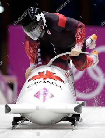 The team from Canada CAN-1, piloted by Lyndon Rush and brakeman Lascelles Brown, start their third run during the men's two-man bobsled competition at the 2014 Winter Olympics, in Krasnaya Polyana, Russia
