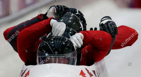 The team from Canada CAN-2, piloted by Lyndon Rush, start a run during the men's four-man bobsled training at the 2014 Winter Olympics, in Krasnaya Polyana, Russia