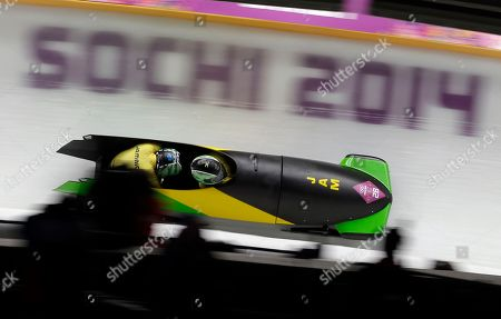 The team from Jamaica JAM-1, piloted by Winston Watts and brakeman Marvin Dixon, takes turn five during the men's two-man bobsled competition at the 2014 Winter Olympics, in Krasnaya Polyana, Russia
