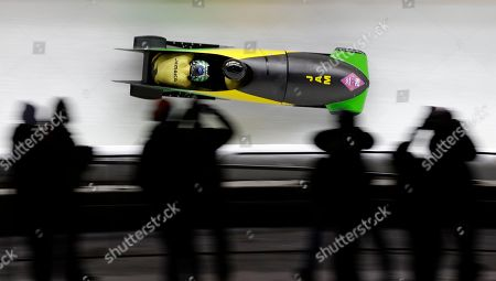 The team from Jamaica JAM-1, piloted by Winston Watts and brakeman Marvin Dixon, take a curve during the men's two-man bobsled competition at the 2014 Winter Olympics, in Krasnaya Polyana, Russia