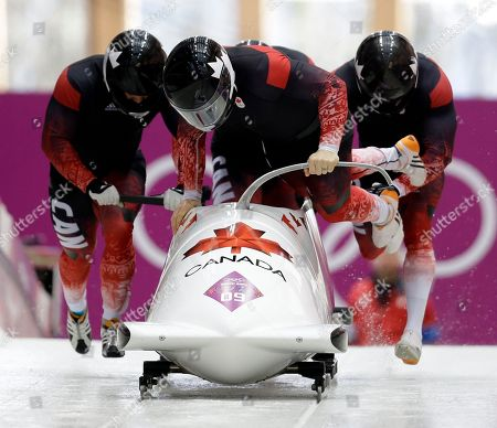 The team from Canada CAN-2, with Lyndon Rush, Lascelles Brown, David Bissett and Neville Wright, start their third run during the men's four-man bobsled competition final at the 2014 Winter Olympics, in Krasnaya Polyana, Russia