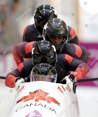 Stock Picture of The team from Canada CAN-2, with Lyndon Rush, Lascelles Brown, David Bissett and Neville Wright, start their third run during the men's four-man bobsled competition final at the 2014 Winter Olympics, in Krasnaya Polyana, Russia