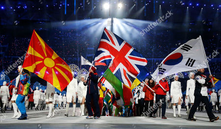 Britain's Elizabeth Yarnold, centre, and South Korea's Lee Kyou-hyuk Lee, right, carry their national flags during the closing ceremony of the 2014 Winter Olympics, in Sochi, Russia