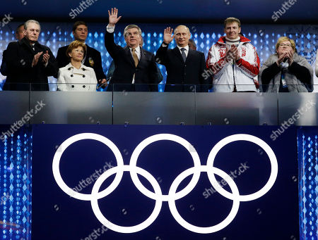 International Olympic Committee (IOC) President Thomas Bach, third from left, and Russian President Vladimir Putin, third from right, wave to spectators during the closing ceremony of the 2014 Winter Olympics, in Sochi, Russia. At far left is former IOC President Jacques Rogge
