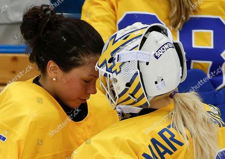Stock Photo of Goalkeeper Valentina Wallner of Sweden greets goalkeeper Kim Martin Hasson at the end of the second period of the 2014 Winter Olympics women's semifinal ice hockey game against the USA at Shayba Arena, in Sochi, Russia. Wallner was replaced by Hasson after giving up five goals