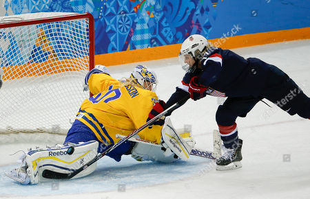 Stock Image of Goalkeeper Kim Martin Hasson of Sweden blocks a penalty shot by Jocelyne Lamoureux of the United States during the third period of the 2014 Winter Olympics women's semifinal ice hockey game at Shayba Arena, in Sochi, Russia