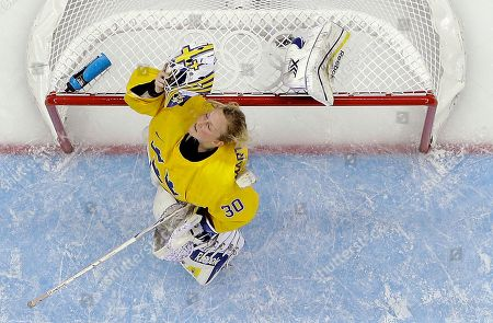 Stock Photo of Goalkeeper Kim Martin Hasson of Sweden adjusts her helmet after allowing a goal by the USA during the third period of the 2014 Winter Olympics women's semifinal ice hockey game at Shayba Arena, in Sochi, Russia. The USA won 6-1