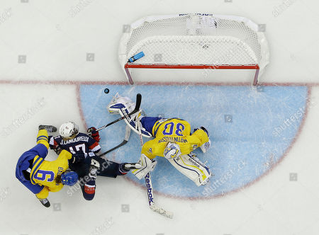Stock Picture of Goalkeeper Kim Martin Hasson of Sweden blocks a shot by Jocelyne Lamoureux of the United States as Lina Backlin of Sweden defends during the third period of the 2014 Winter Olympics women's semifinal ice hockey game at Shayba Arena, in Sochi, Russia. The USA won 6-1