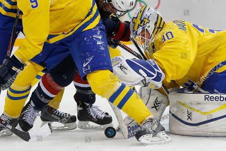 Goalkeeper Kim Martin Hasson of Sweden dives on a puck during the third period of the 2014 Winter Olympics women's semifinal ice hockey game against the Unted States at Shayba Arena, in Sochi, Russia. USA defeated Sweden 6-1
