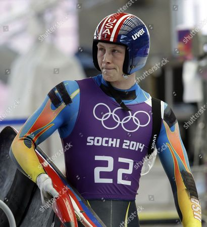 Aidan Kelly of the United States walks off the track after a training session for the men's singles luge at the 2014 Winter Olympics, in Krasnaya Polyana, Russia