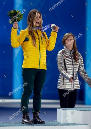 Women's snowboard halfpipe silver medalist Torah Bright of Australia, left, smiles as gold medalist Kaitlyn Farrington of the United States applauds during their medals ceremony at the 2014 Winter Olympics, in Sochi, Russia